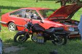 Электромотоцикл Suzuki на фоне электромобиля Opel Monza